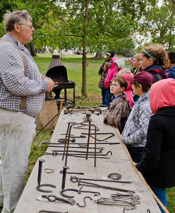 Blacksmith teaching school kids